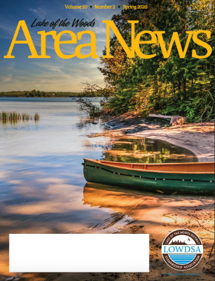 Magazine cover with green canoe on shore